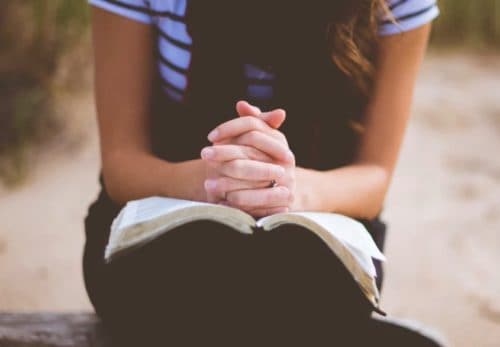 Frau faltet Hände über Bibel
